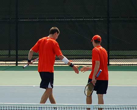 Auburn tennis doubles partners shake hands after winning point