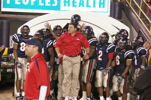 Ed Orgeron leads the Rebels onto the field