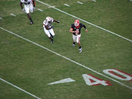 Georgia quarterback Matthew Stafford runs away from Auburn defender